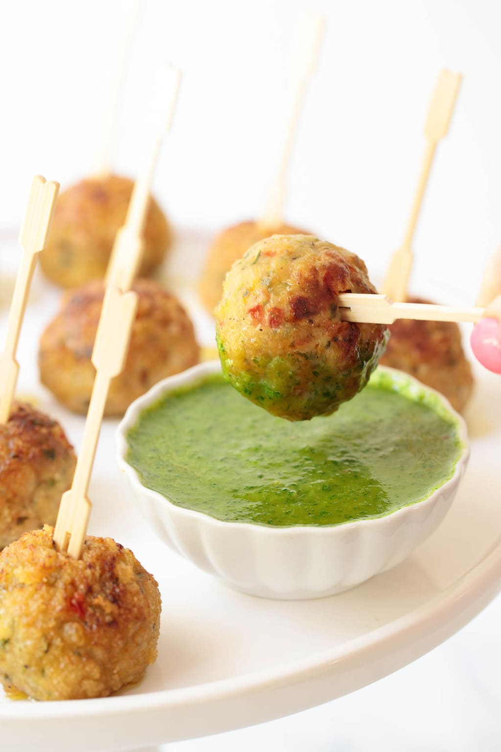 Closeup photo of a platter of Baked Lemongrass Chicken Meatballs with one being dipped in lemongrass cilantro dipping sauce.