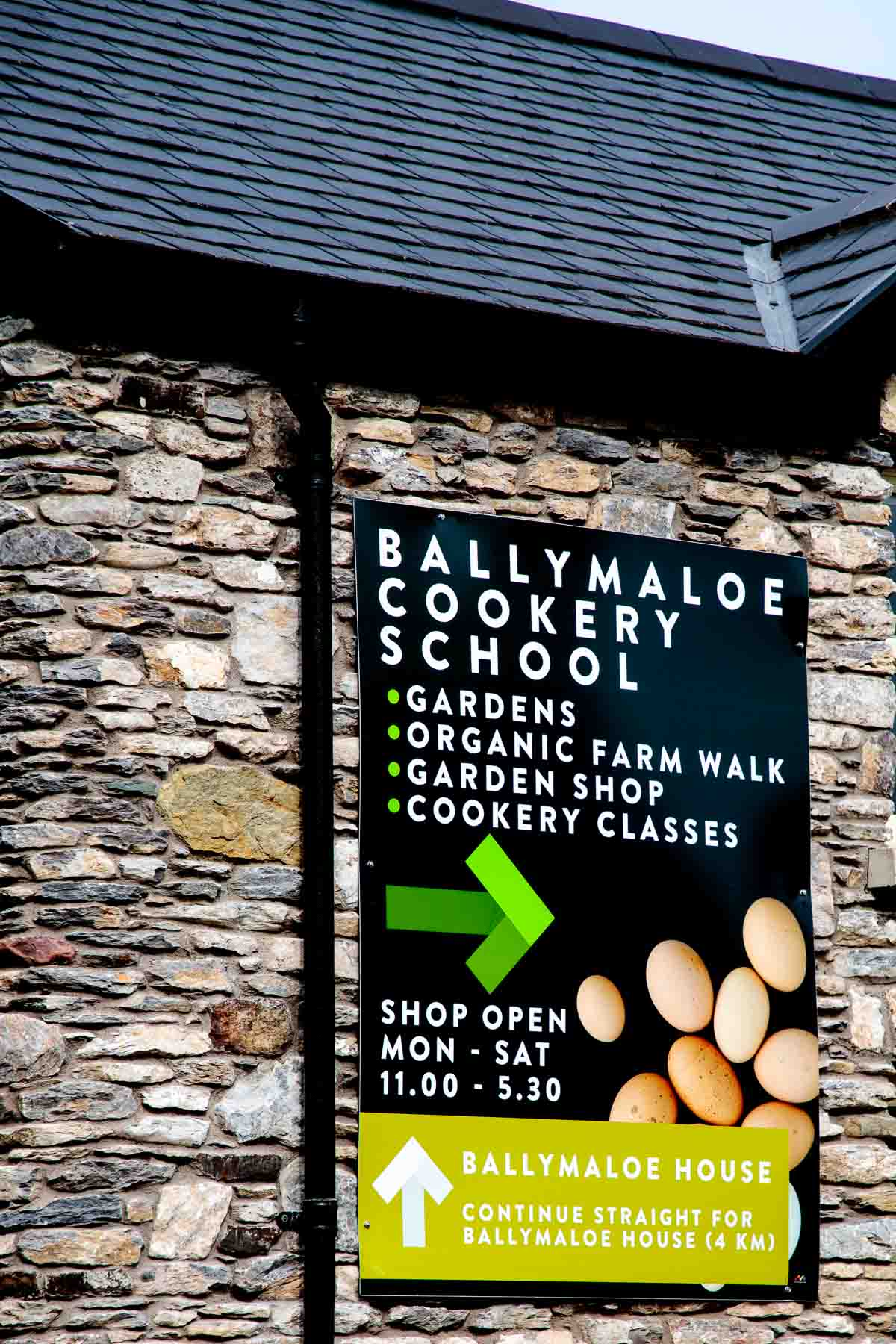 Photo of the road sign for the Ballymaloe Cookery School on a stone building.