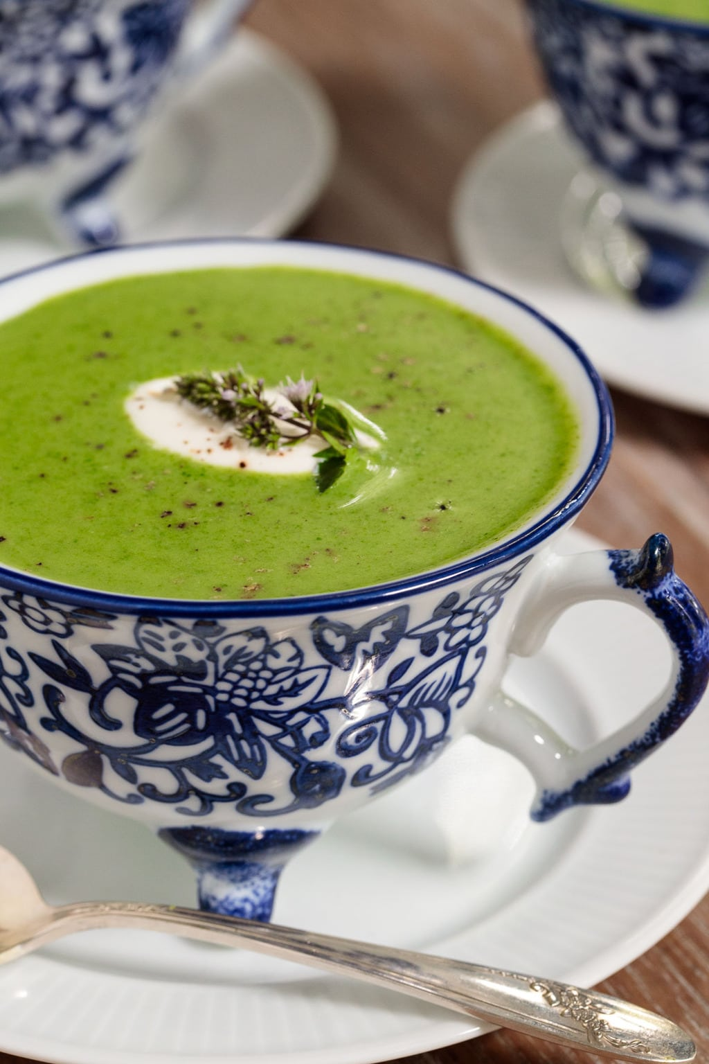 Closeup photo of a cup of Ballymaloe Fresh Spinach Soup on a white plate with other cups of soup in the background.