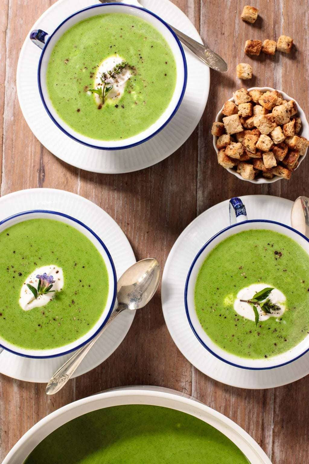 Overhead vertical photo of Fresh Spinach Soup in small blue and white patterned serving bowls with a bowl of croutons nearby.
