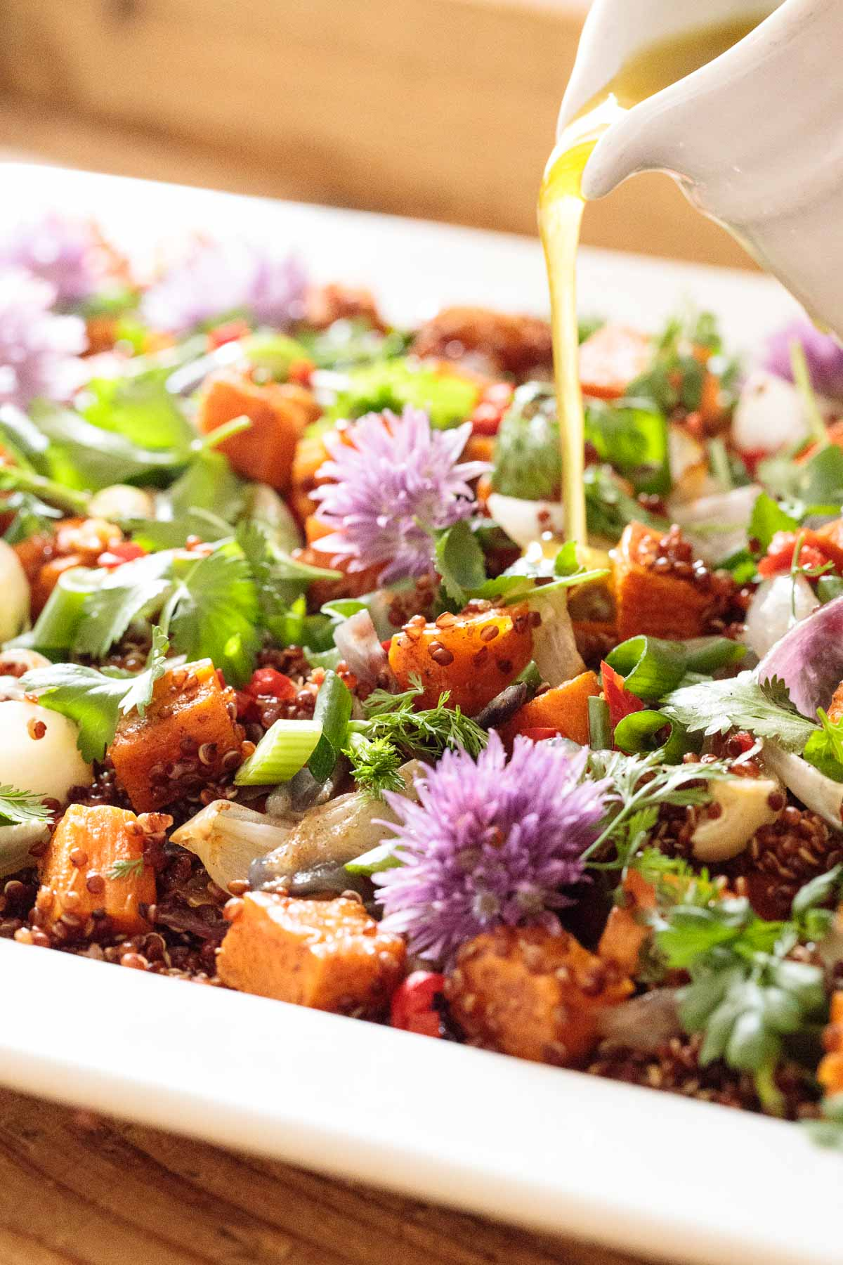 Photo of a Ballymaloe Quinoa Sweet Potato Salad on a white platter with the dressing being drizzled over the salad.