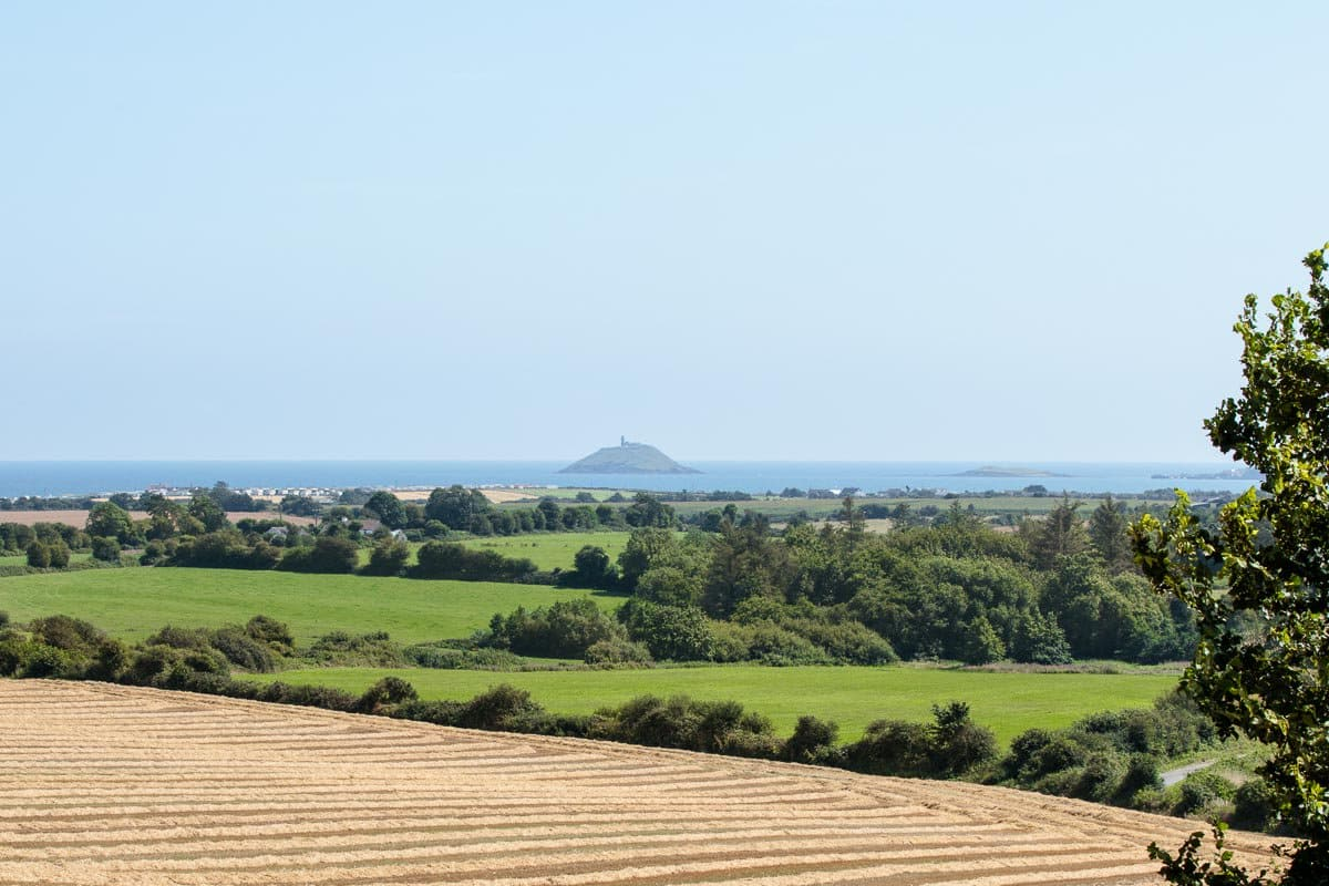 Photo of the farmlands surrounding the Ballymaloe Cookery School with the Ballycotton lighthouse and the Irish Sea in the background.