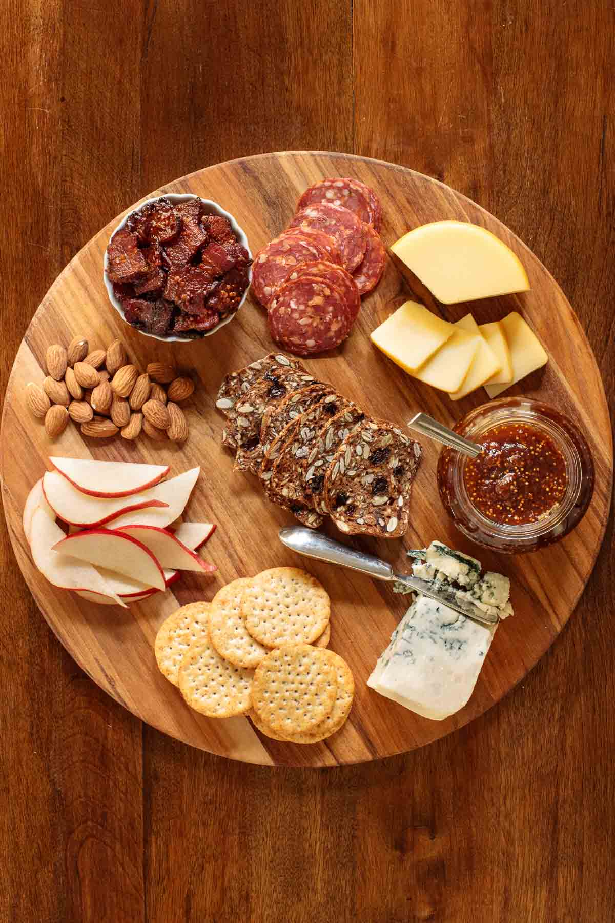 Overhead photo of a wood appetizer tray with sausages, cheeses, apples, maple mustard bacon, almonds and featuring Easy Balsamic Fig Jam.