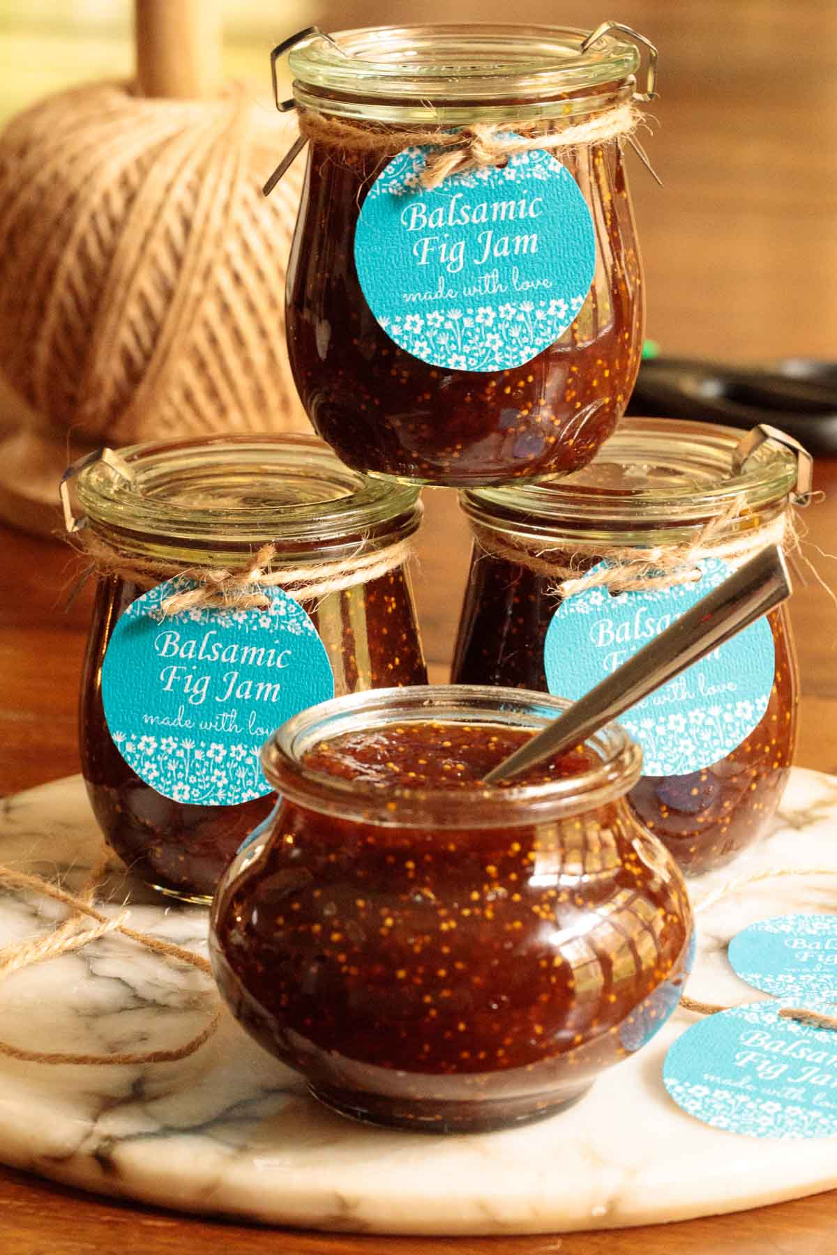 Photo of jars of Easy Balsamic Fig Jam with customized labels attached resting on a marble appetizer tray.