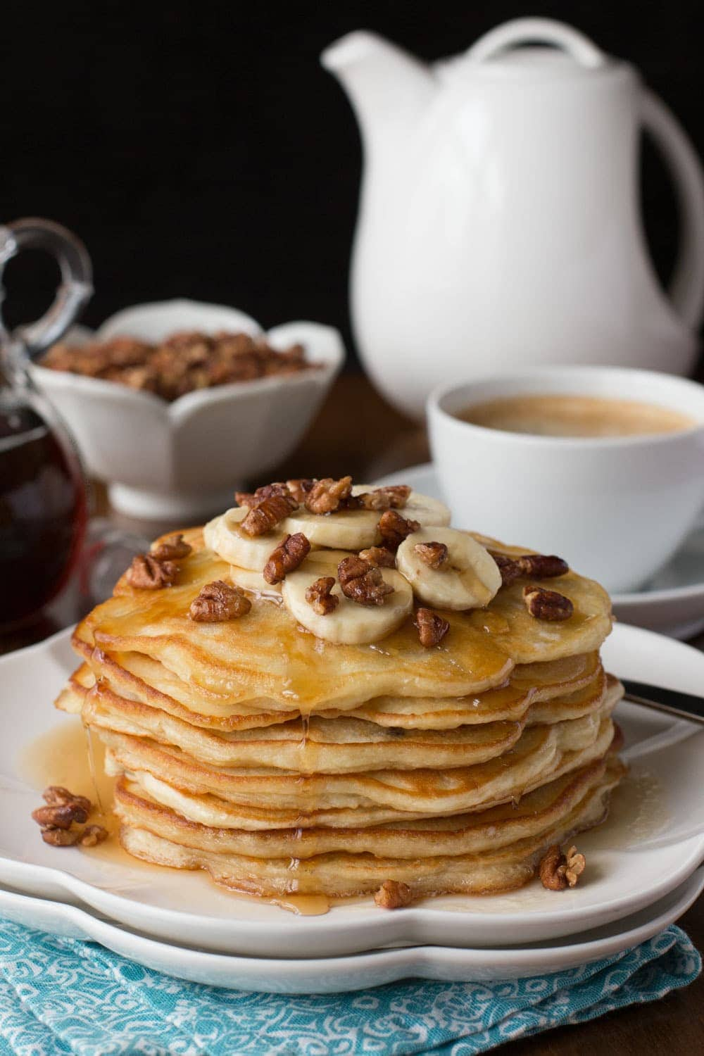Vertical picture of Banana Pancakes with Maple Molasses Pecans stacked on a white plate with coffee and pecans in the background
