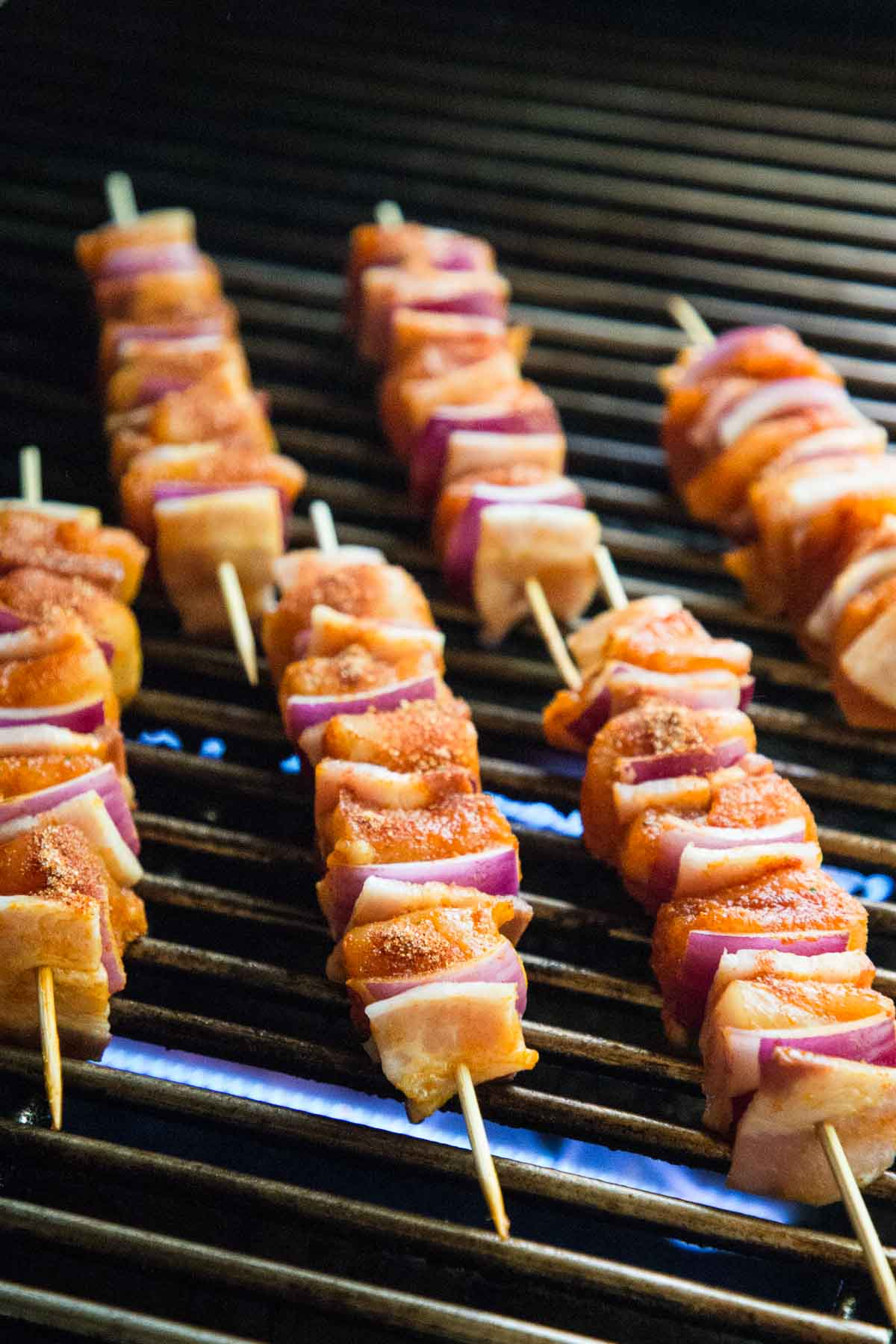 Closeup photo of Bacon Bourbon Barbecued Chicken Skewers just placed on the grill.