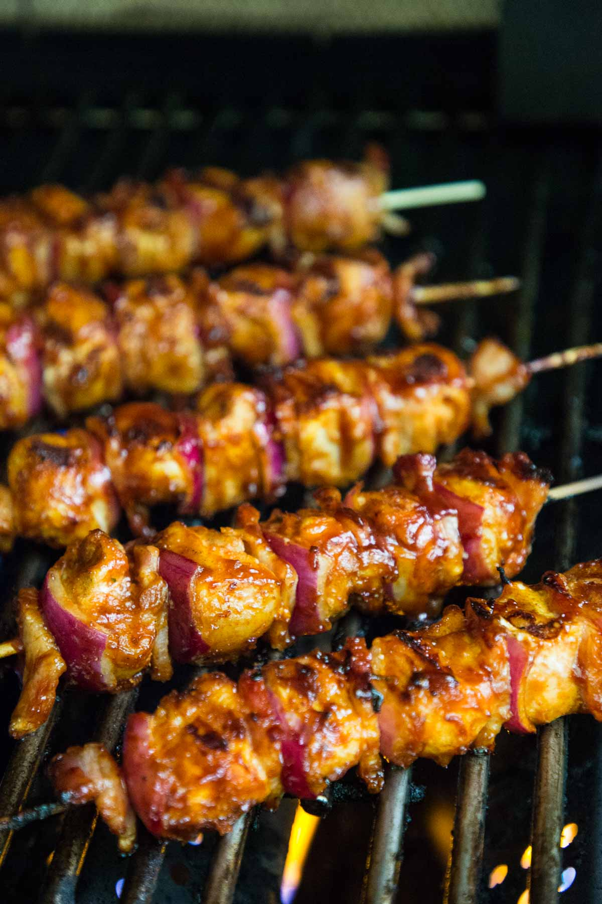 Process photo of Bacon Bourbon Barbecued Chicken Skewers well into the grilling stage.