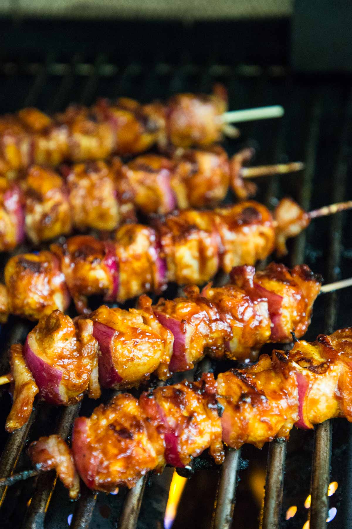 Vertical photo of Barbecued Chicken Skewers on the grill.