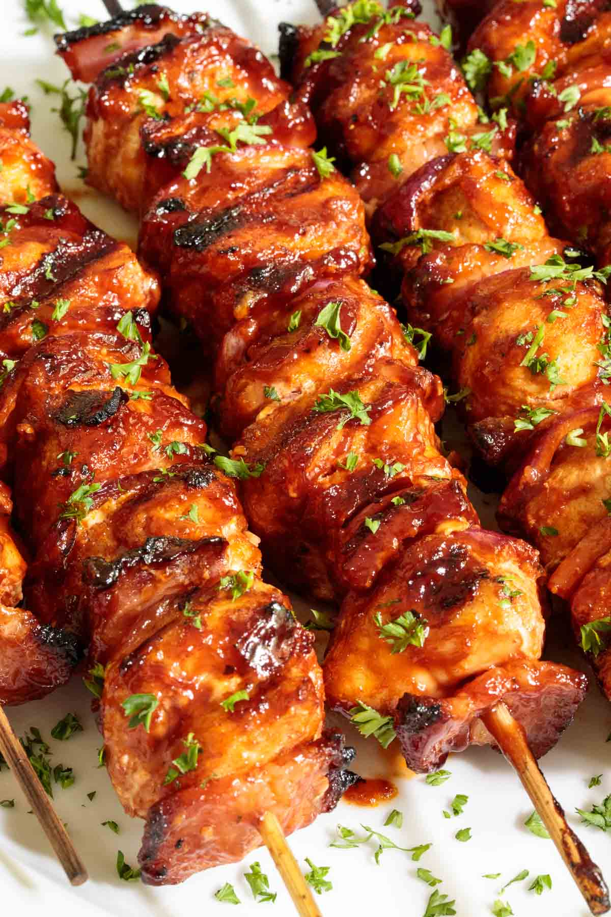 Ultra closeup photo of a row of Bacon Bourbon Barbecued Chicken Skewers finished and garnished with cilantro.