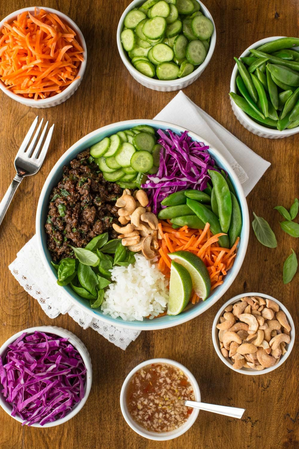 Overhead vertical photo of Thai Basil Beef Rice Bowls with all the toppings in separate surrounding bowls on a wooden table.