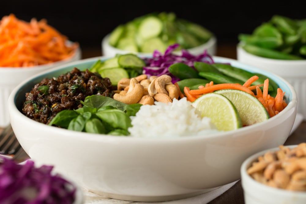 Closeup photo of a 30 Minute Thai Basil Beef Bowl surrounded by mini prep bowls of the individual ingredients.