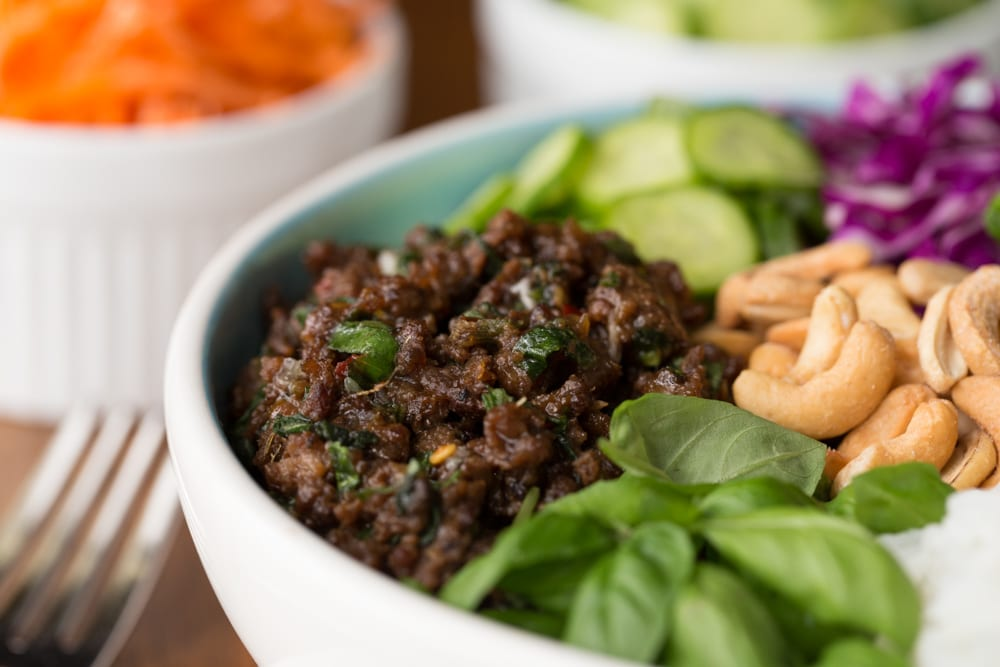 Closeup photo of a 30 Minute Thai Basil Beef Bowl surrounded by individual ingredient bowls.