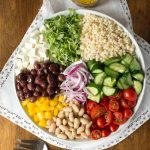 Overhead picture of Best Ever Greek Salad with ingredients grouped together in a white bowl