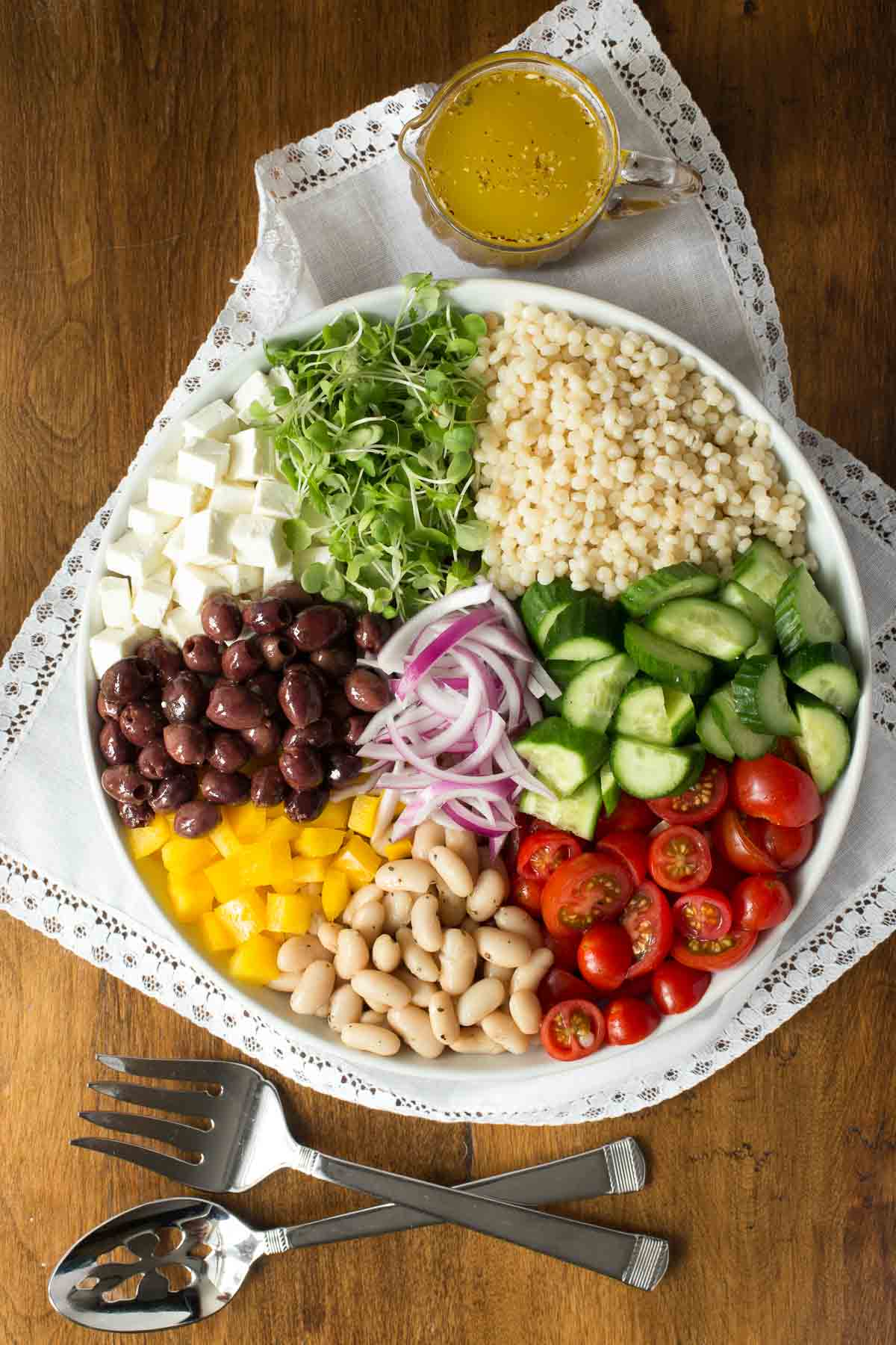Overhead photo of a plate filled with Best Ever Greek Salad components on a white lace cloth.