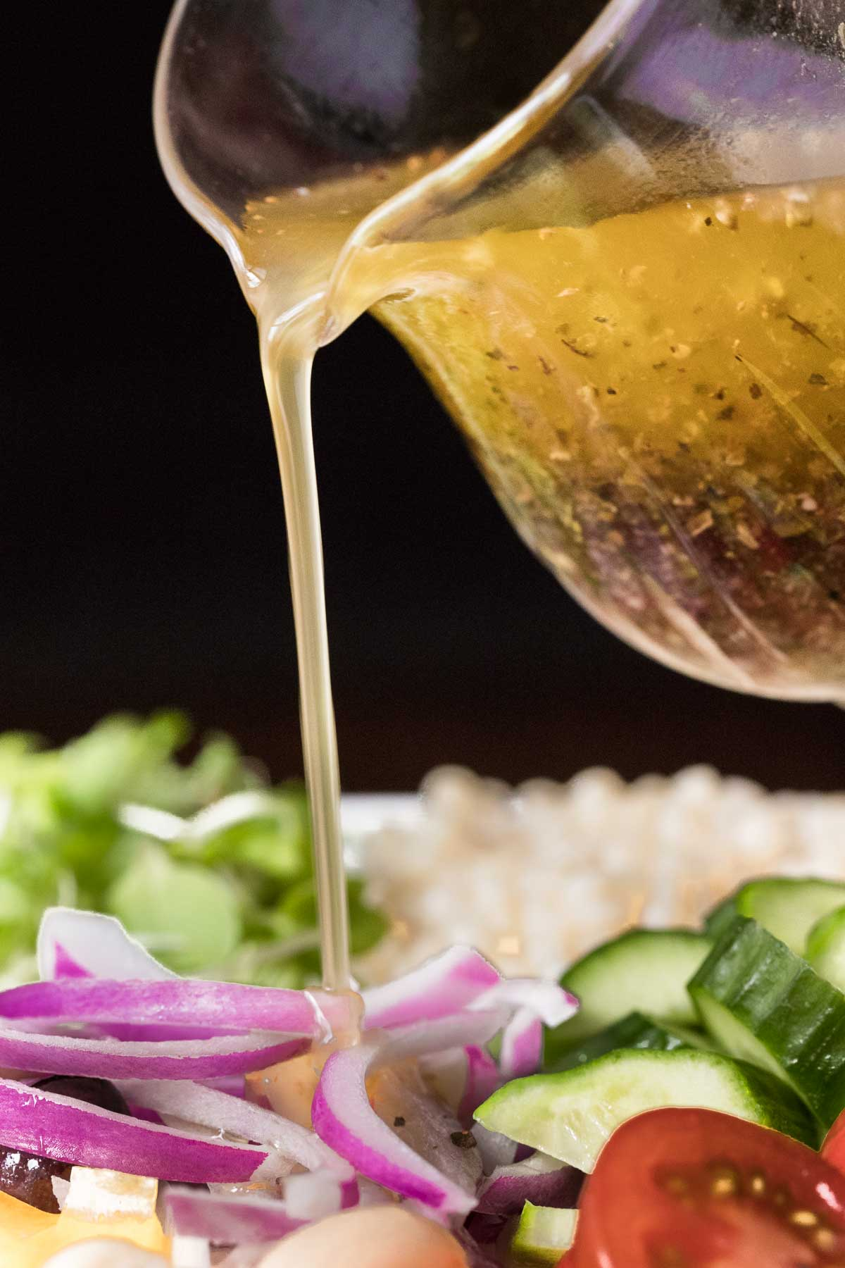 Closeup photo of a pitcher of Zoe's Copycat Dressing being poured on to a Best Greek Salad
