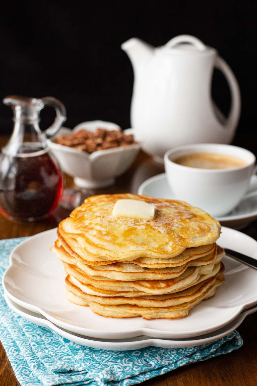 Vertical photo of a stack of Best Ever Pancakes on a white plate with syrup, nuts and a cup of coffee in the background.