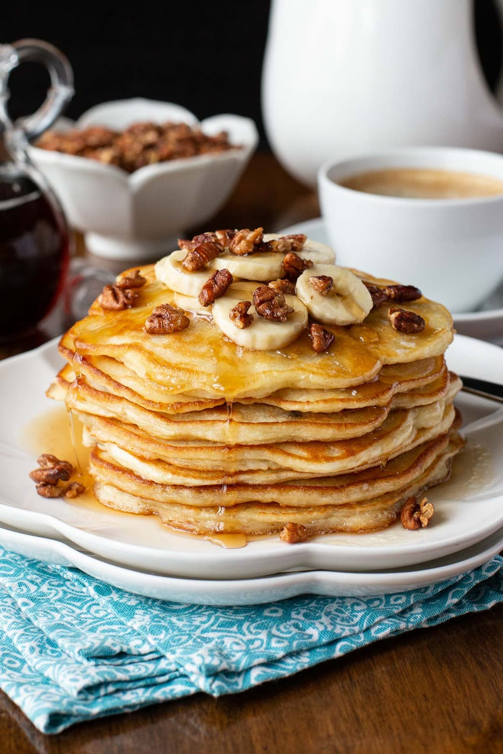 Vertical photo of a stack of Best Ever Pancakes topped with bananas and pecans.