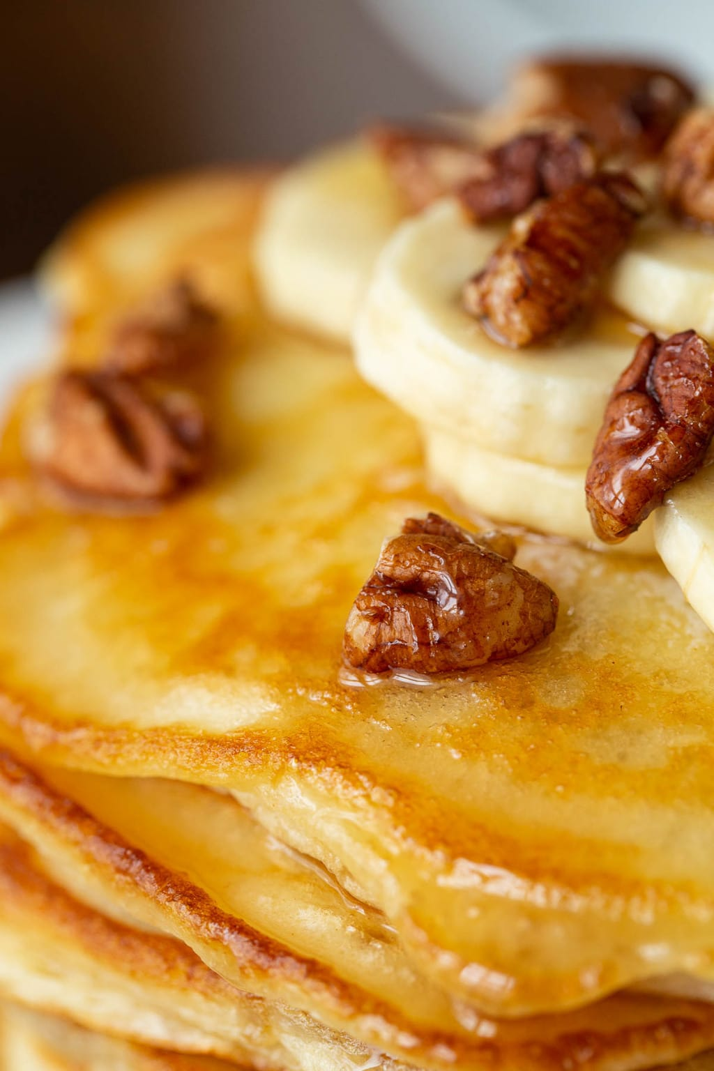Ultra closeup vertical photo of the top of a stack of Best Ever Pancakes garnished with pecans, bananas and maple syrup.