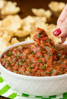Close up vertical picture of salsa in a white bowl with chips