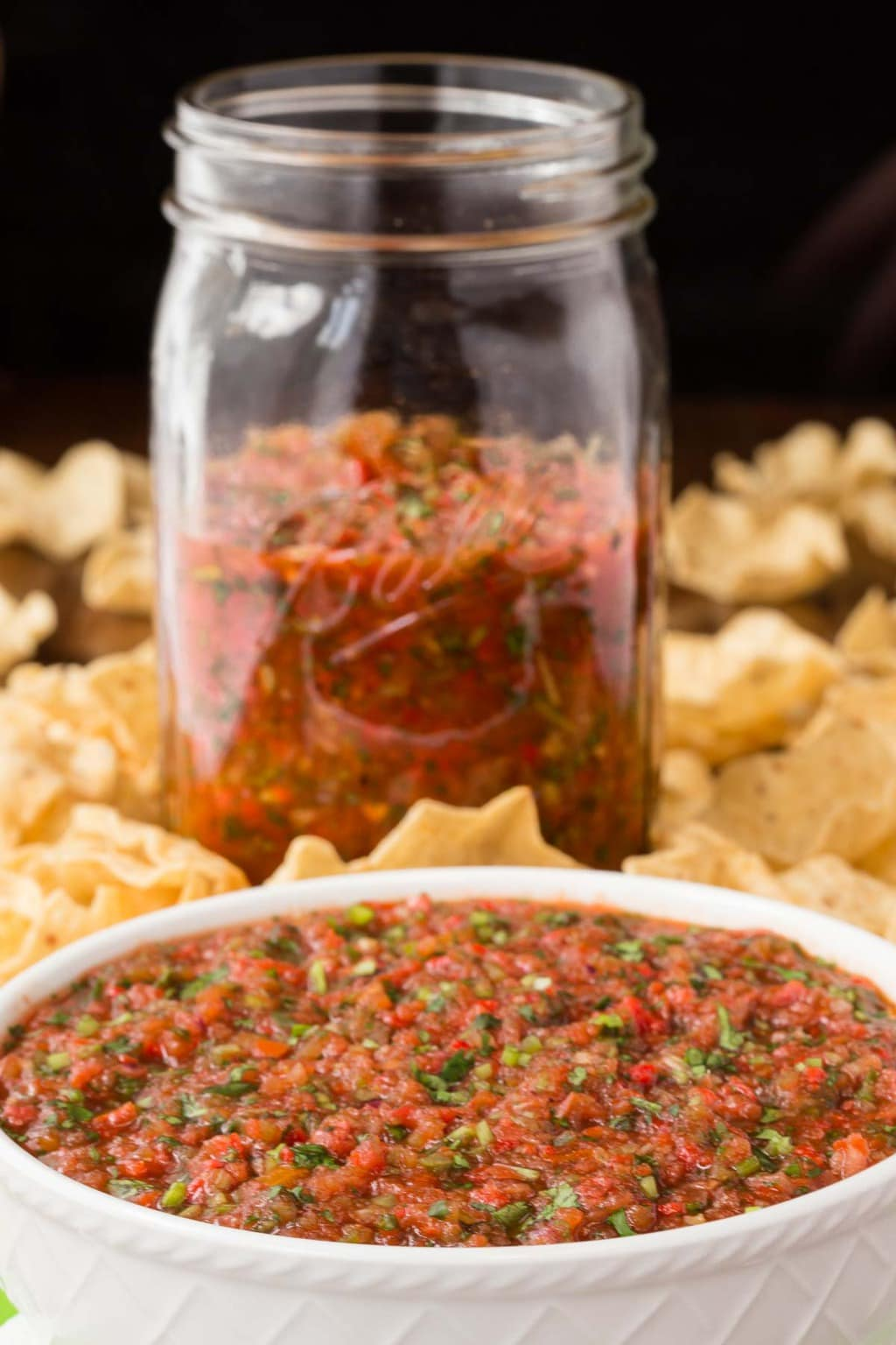 Photo of a white bowl of Best Ever, Super Easy Salsa with extra salsa behind it in a Ball jar, surrounded by tortilla chips.