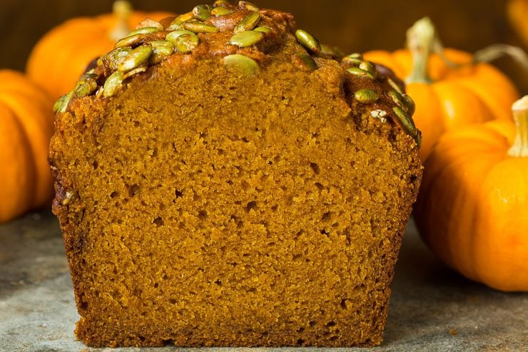 A closeup interior photo of a loaf of Better Than Starbucks Pumpkin Bread surrounded by mini pumpkins.