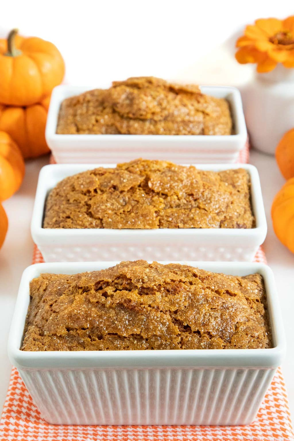 Vertical photo of three mini loaves of Better Than Starbucks Pumpkin Bread (One-Bowl, No-Mixer!) lined up on an orange and white cloth surrounded by mini pumpkins.