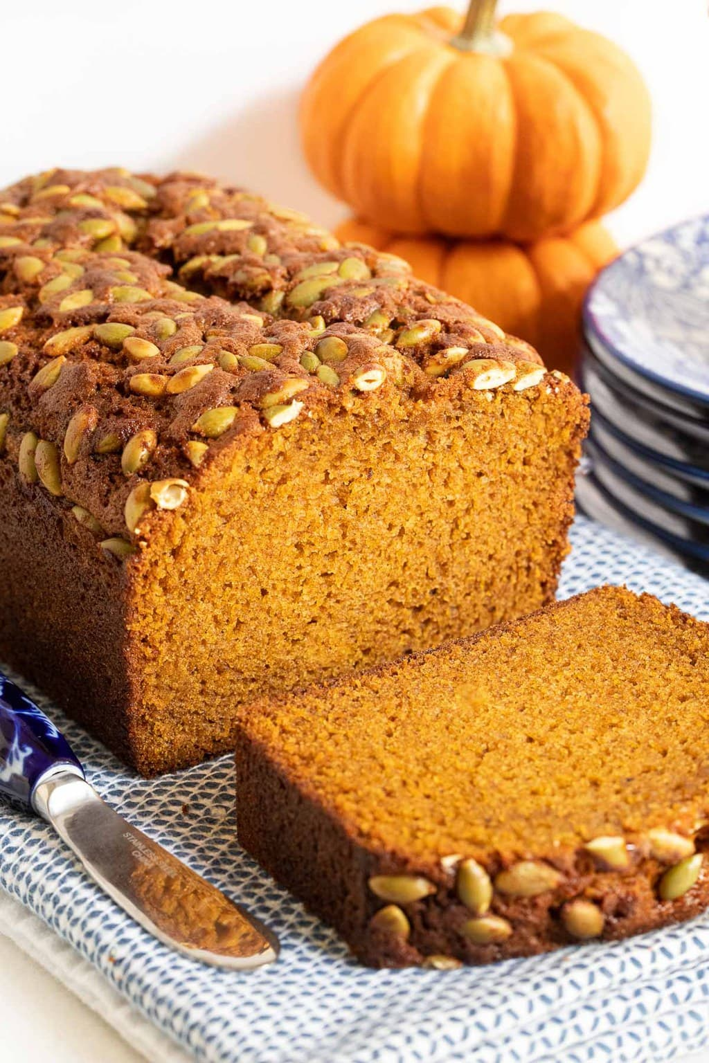 Closeup vertical photo of a loaf of Better Than Starbucks Pumpkin Bread (One-Bowl, No-Mixer!) with a slice cut on a blue and white patterned cloth.