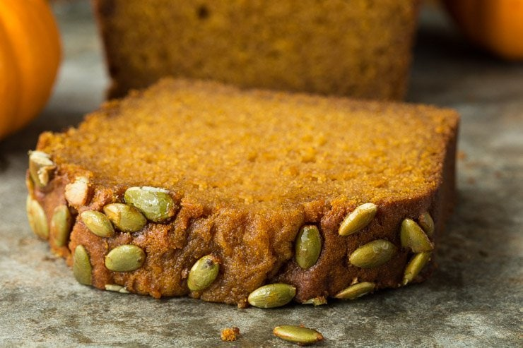 Closeup photo of a thick slice of Better Than Starbucks Pumpkin Bread on a baking pan with a loaf and mini pumpkins in the background.