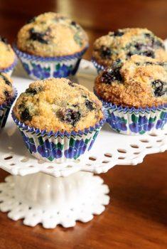 Horizontal closeup photo of a batch of Better than Starbucks Blueberry Muffins on a white lattice pedestal serving plate.