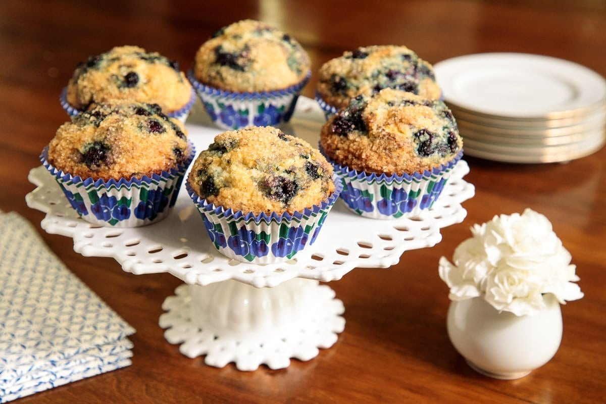 Horizontal photo of Better than Starbucks Blueberry Muffins on a white lattice pedestal cake stand in blue, green and white patterned cupcake liners.