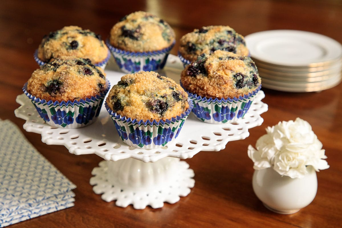 Photo of a batch of Copycat Starbuck's Blueberry Muffins on a white lace porcelain pedestal stand surrounded by serving supplies and a white carnation.