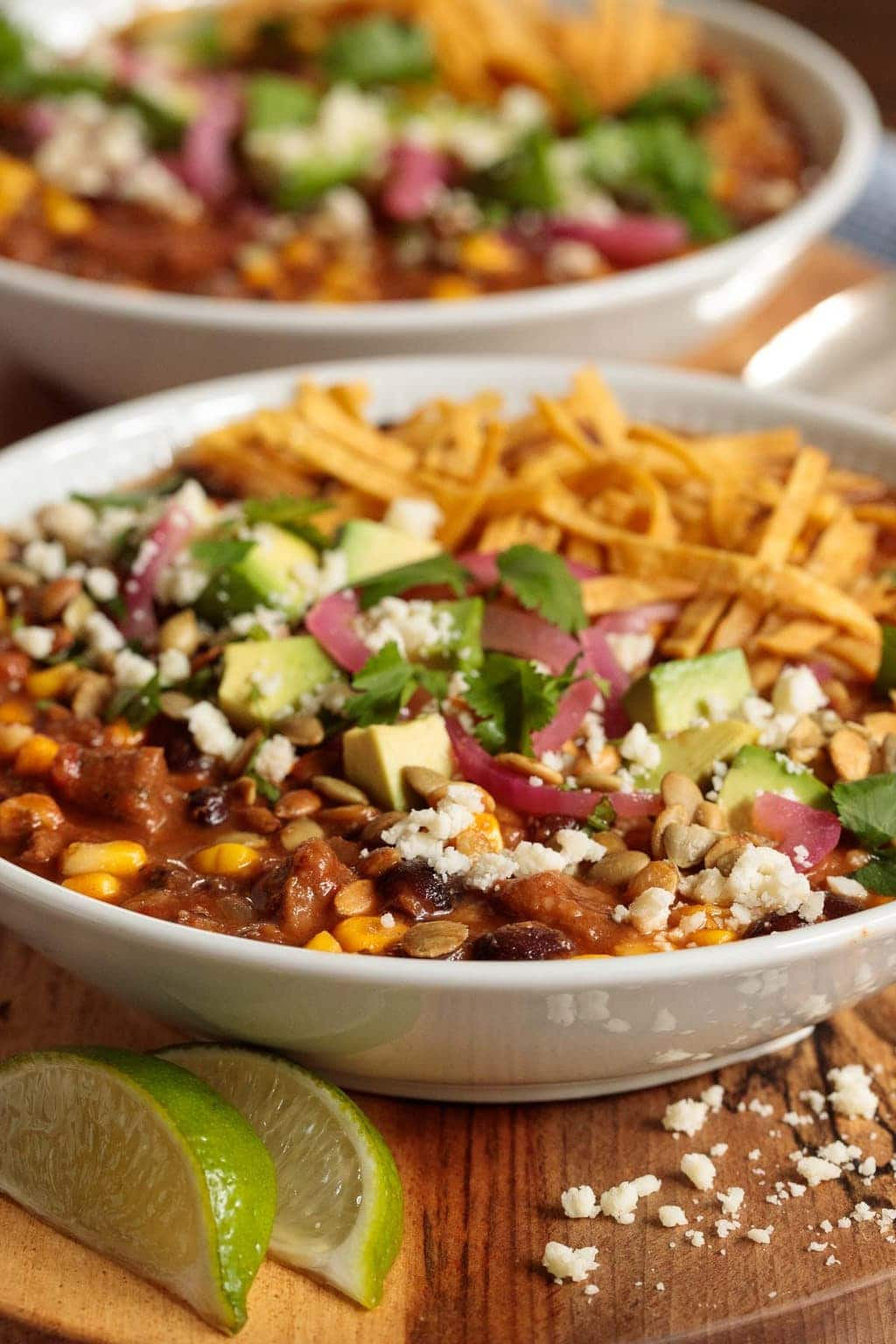 Vertical picture of black bean beef and tortilla soup in white bowls loaded with toppings