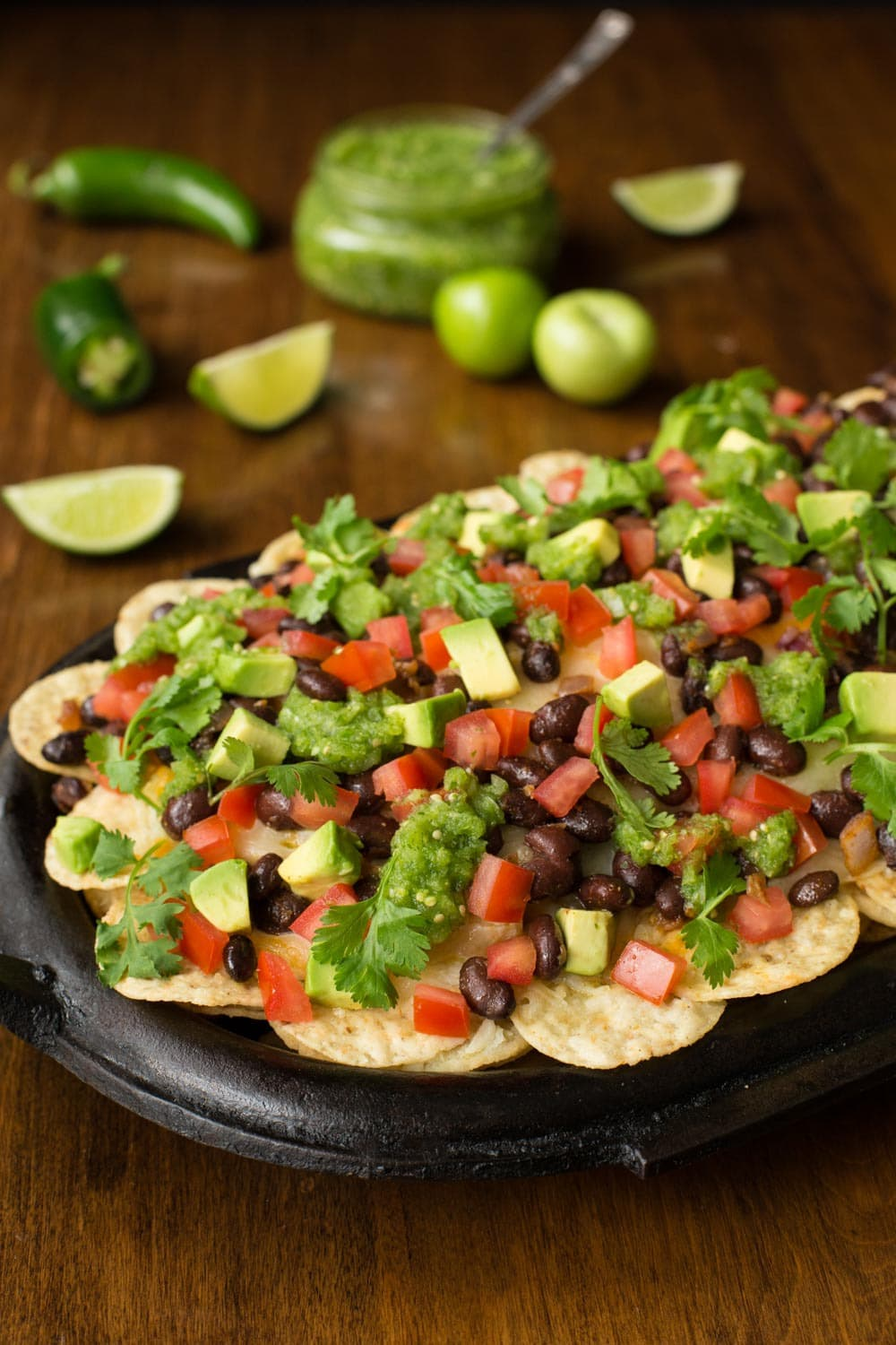 Photo of a cast iron skillet with Black Bean Nachos with Salsa Verde with limes, tomatillos and peppers on the table in the background.