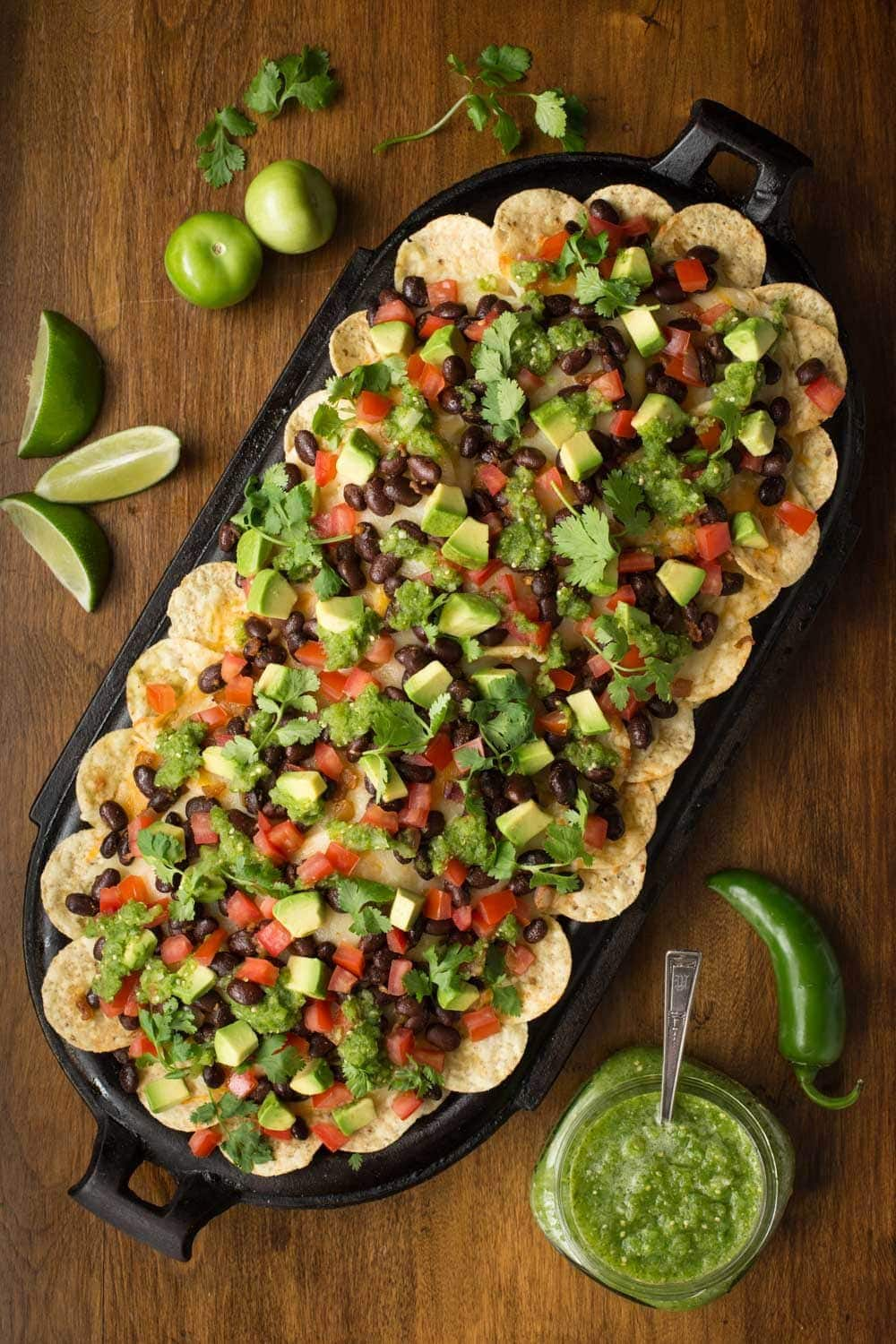 Overhead photo of a black oblong cast iron skillet with Black Bean Nachos with Salsa Verde surrounded by limes, tomatillos, peppers and lime wedges.