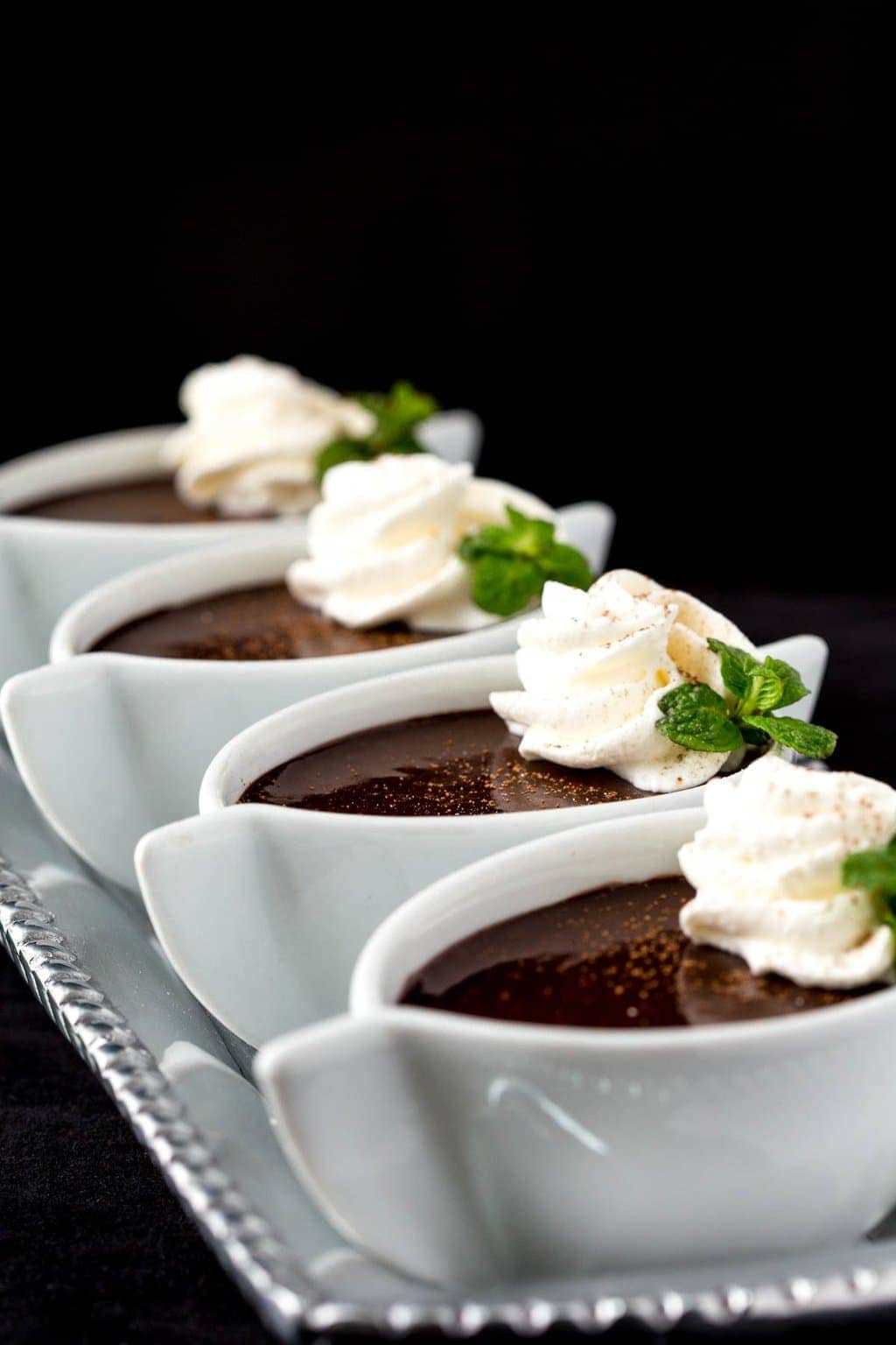 Photo of a row of Blender Chocolate Pots de Crème in white individual serving cups with a black background.