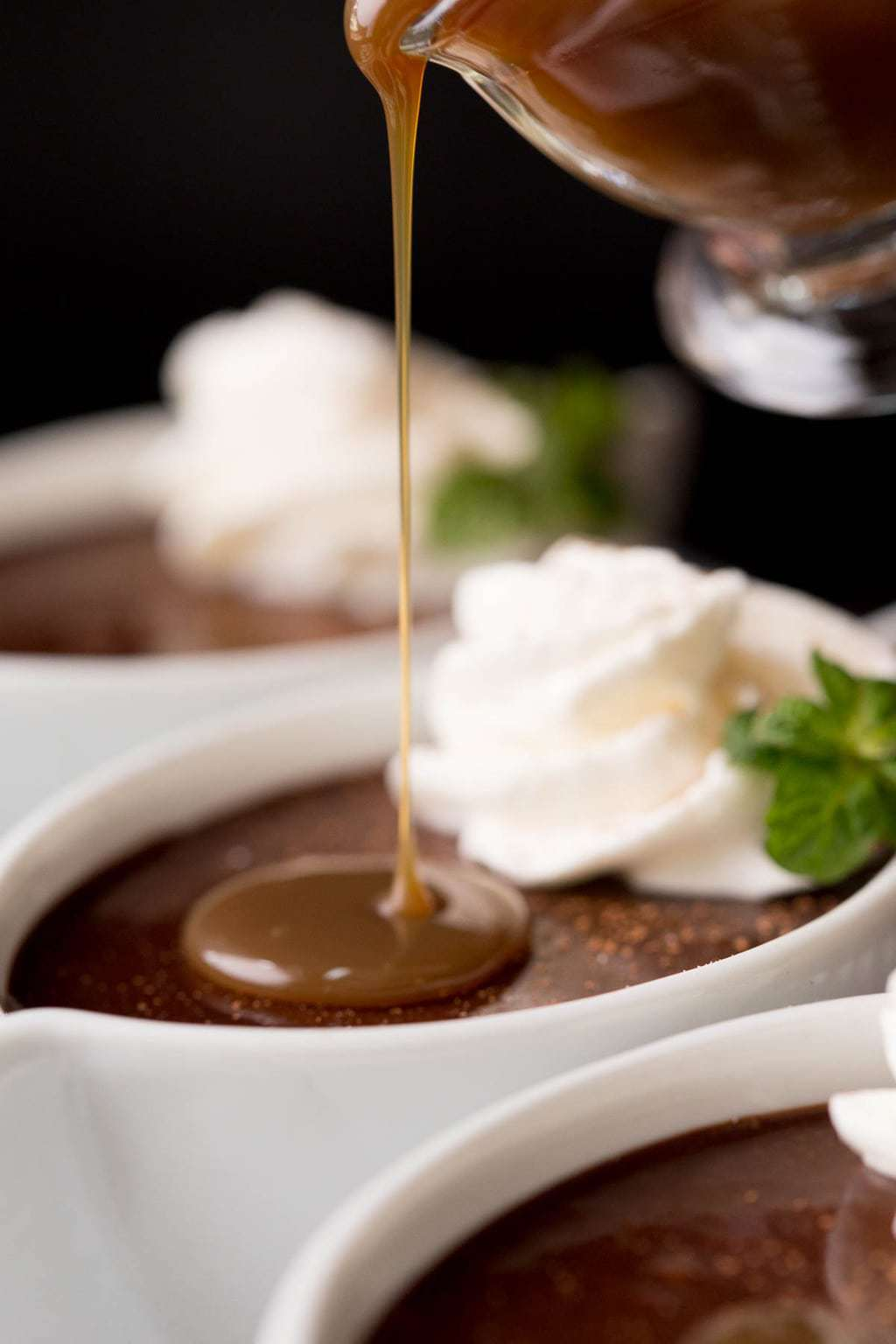 Closeup photo of a dessert cup of Blender Chocolate Pots de Crème with Bailey's Irish Cream sauce being poured over it.