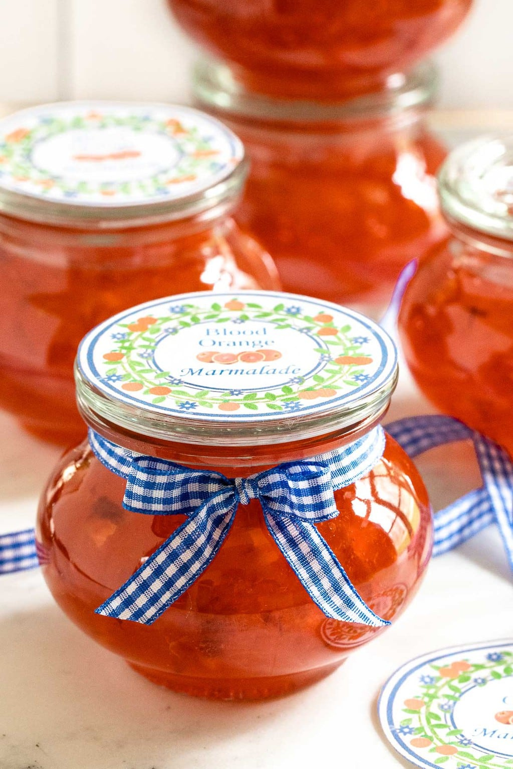Vertical photo of Blood Orange Marmalade in small glass Weck jars decorated with custom gift labels and ribbon.