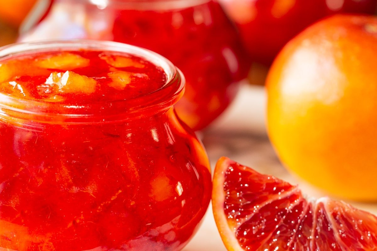 Horizontal ultra closeup photo of Blood Orange Marmalade in glass Weck canning jars with a wedge of a blood orange in the foreground.