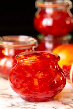 Vertical ultra closeup photo of jars of Blood Orange Marmalade.