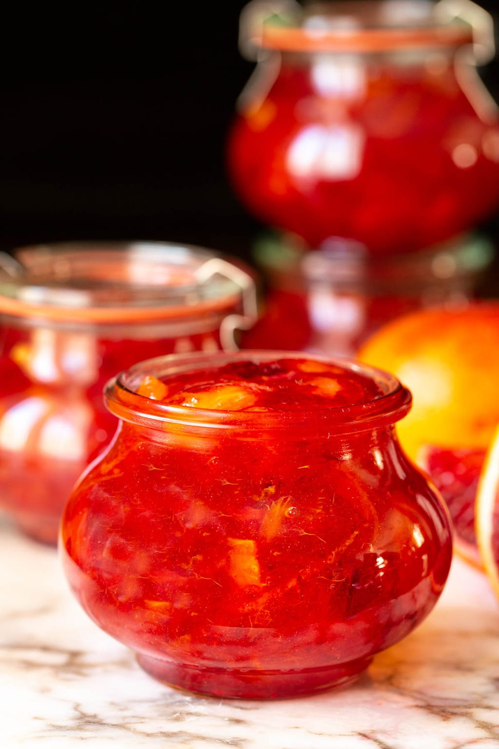 Vertical closeup photo of Weck glass jars of Blood Orange Marmalade on a marble countertop.