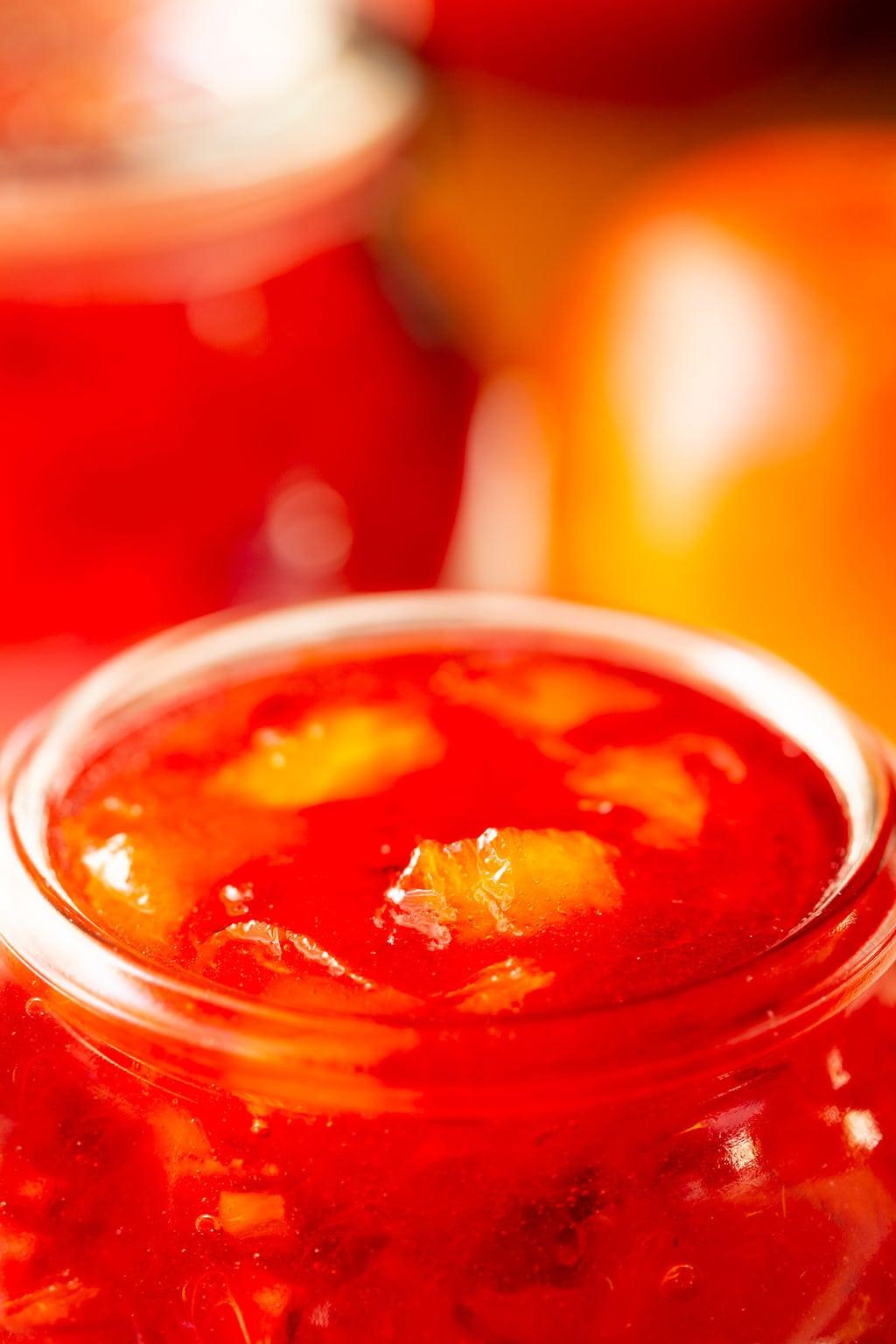 Extreme closeup photo of a Weck glass jar of Blood Orange Marmalade.