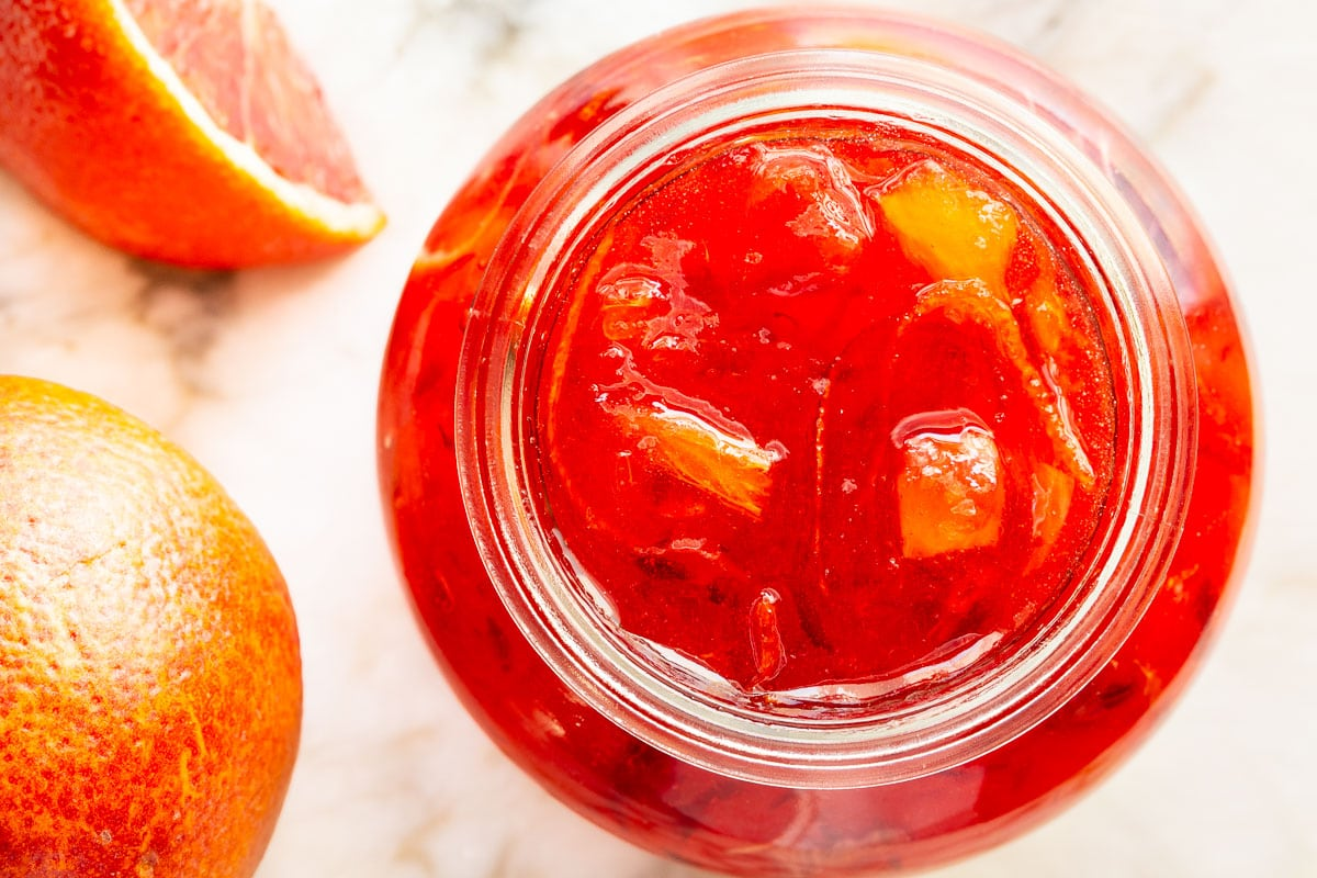 Horizontal overhead photo of a jar of Blood Orange Marmalade surrounded by blood oranges and wedges of blood oranges.