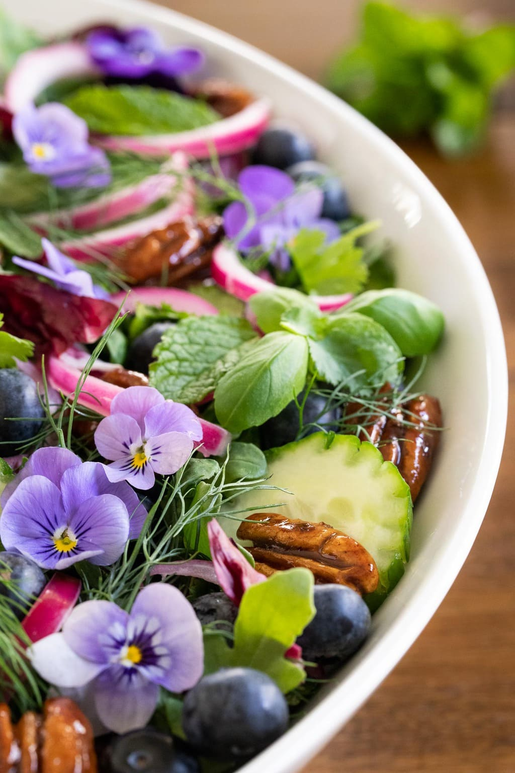 Vertical closeup photo of a Blueberry Arugula Herb Salad garnished with pickled onions, candied pecans and viola flowers.