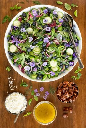 Vertical overhead picture of Blueberry Arugula Herb Salad in a large white bowl