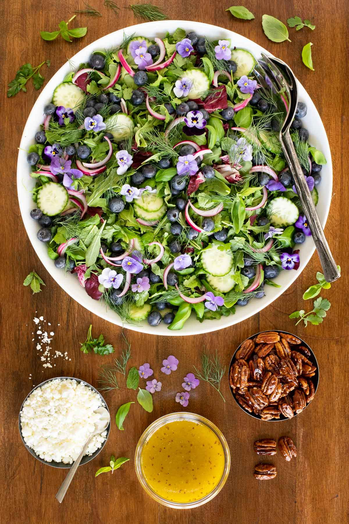 Vertical overhead photo of Blueberry Arugula Herb Salad in a large white presentation bowl on a wood table.
