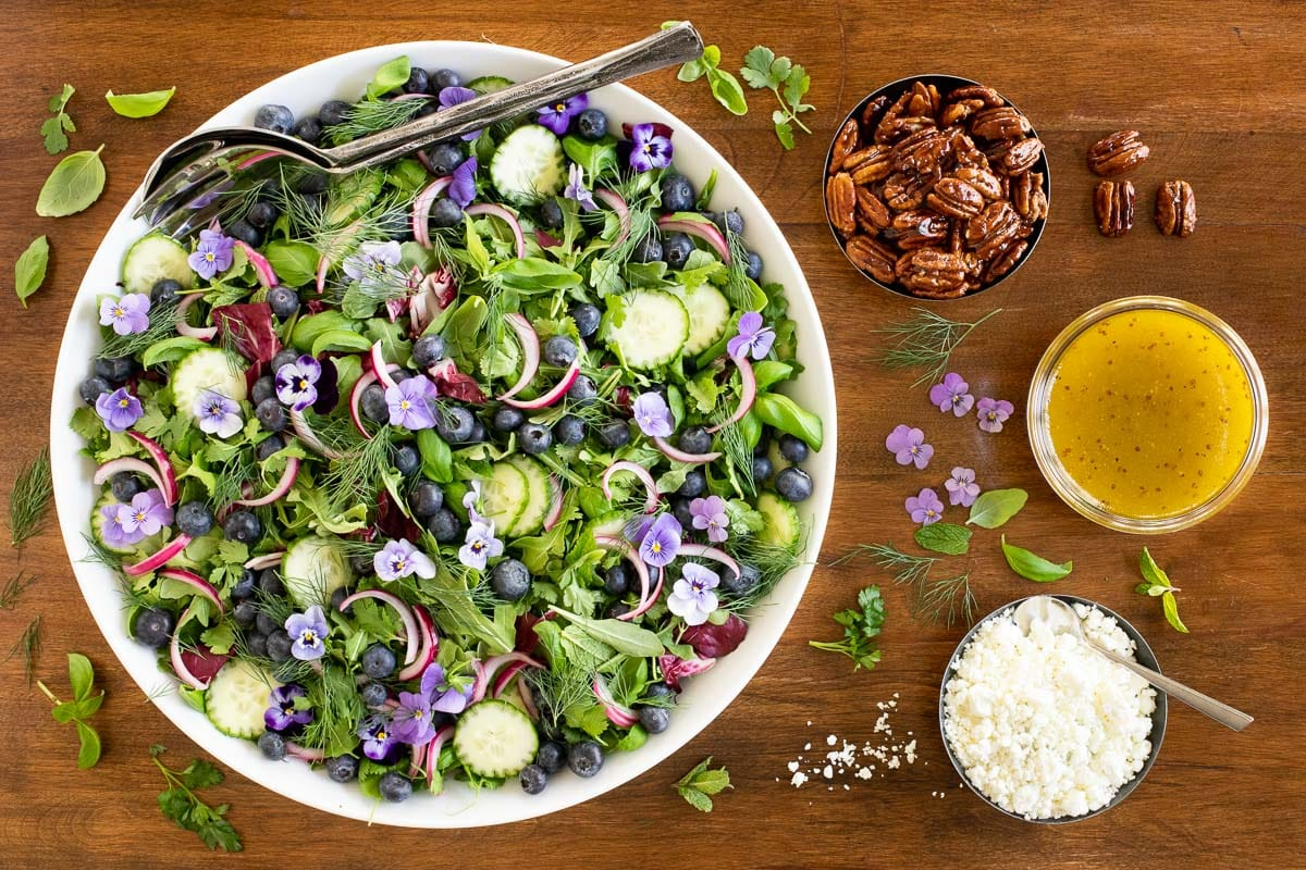 Horizontal overhead photo of a white serving bowl of Blueberry Arugula Herb Salad on a wood table.