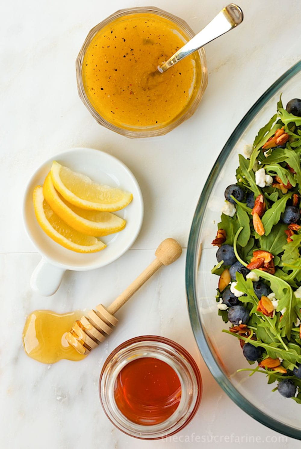 Image from above of the Blueberry Arugula Salad with Honey-Lemon Dressing with bowls of dressing, lemon and honey.