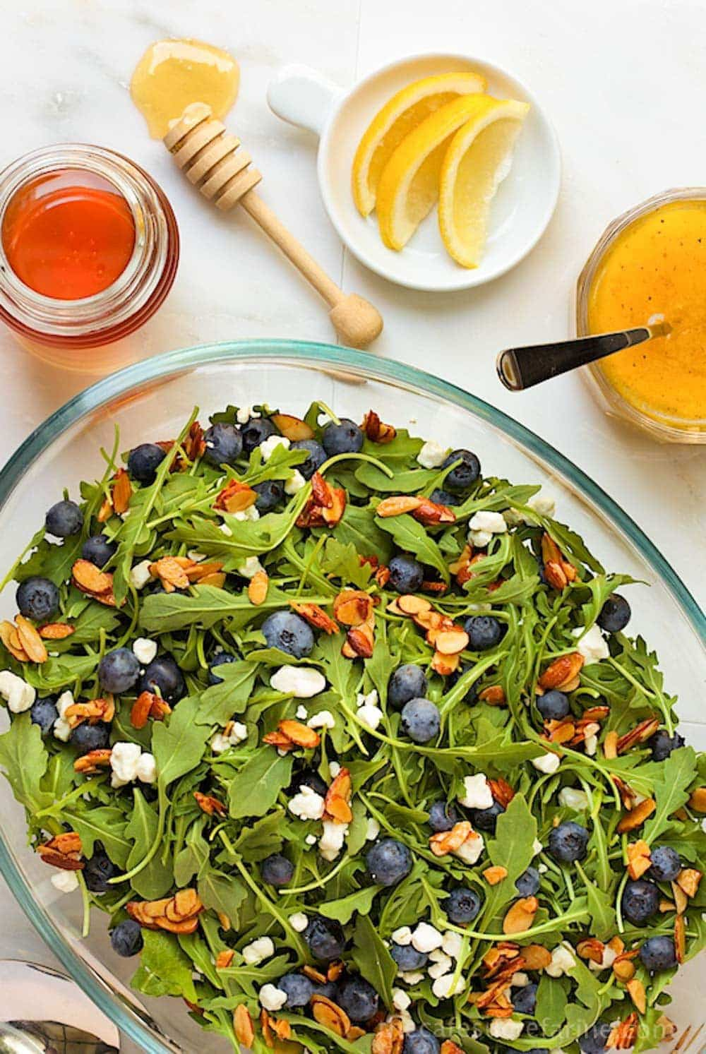 View from above of Blueberry Arugula Salad with Honey-Lemon Dressing in a glass oval serving bowl.