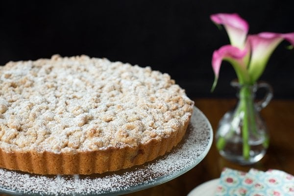 Horizontal image of Blueberry Crumb Cake with pink calla lilies.