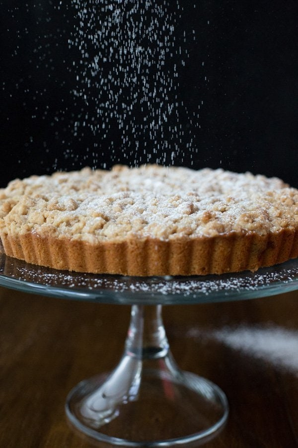 Vertical Image of falling powdered sugar on Blueberry Crumb Cake.